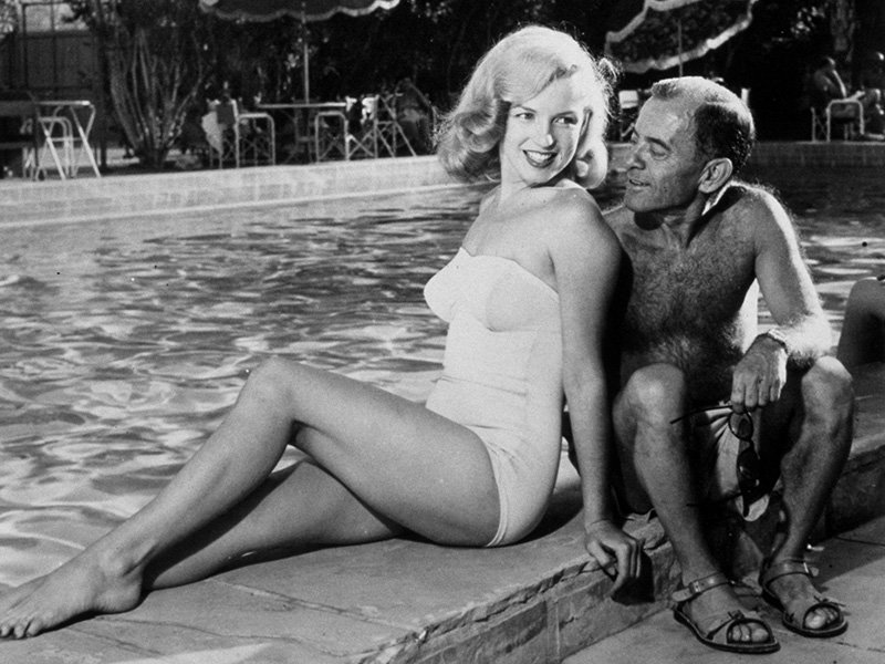 Marilyn Monroe with agent Johnny Hyde, relaxing poolside at her Palm Springs home. Photograph: Rex Features