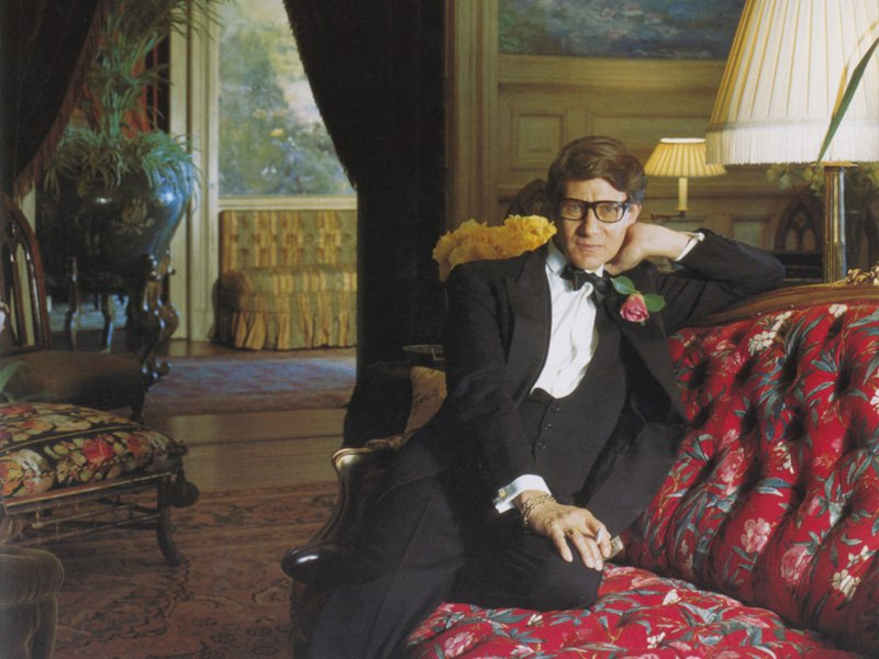 Yves Saint Laurent wearing a tuxedo while reclining on a floral settee in his 19th-century Château Gabriel at Bénerville, France, circa December 1983. The wall behind him features a water-lily mural by Paul Meriguet. Image copyright Condé Nast Archive/Corbis