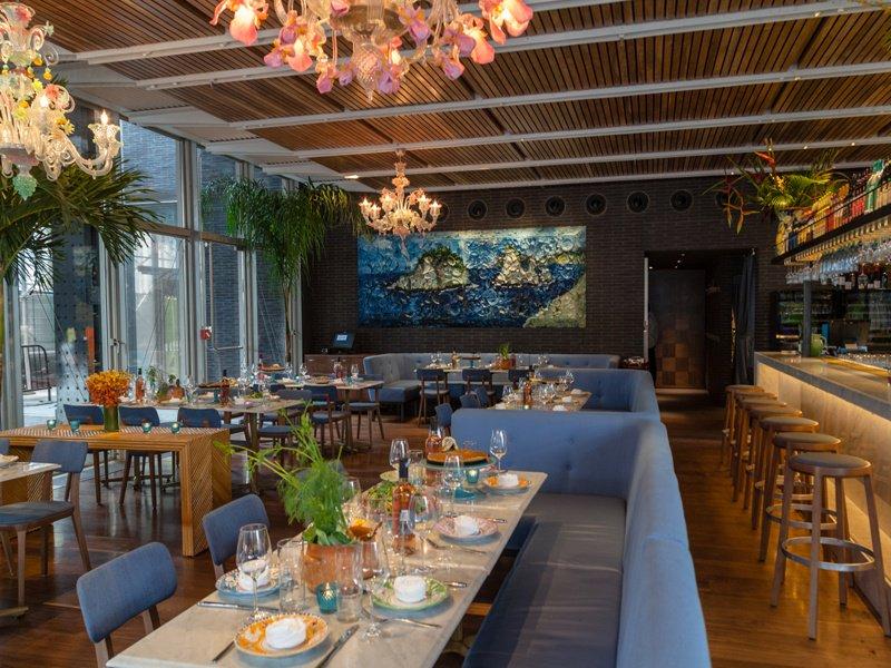 Elegant white marble tables sit below impressive Murano chandeliers in the Renzo Piano-designed Santina restaurant in New York.