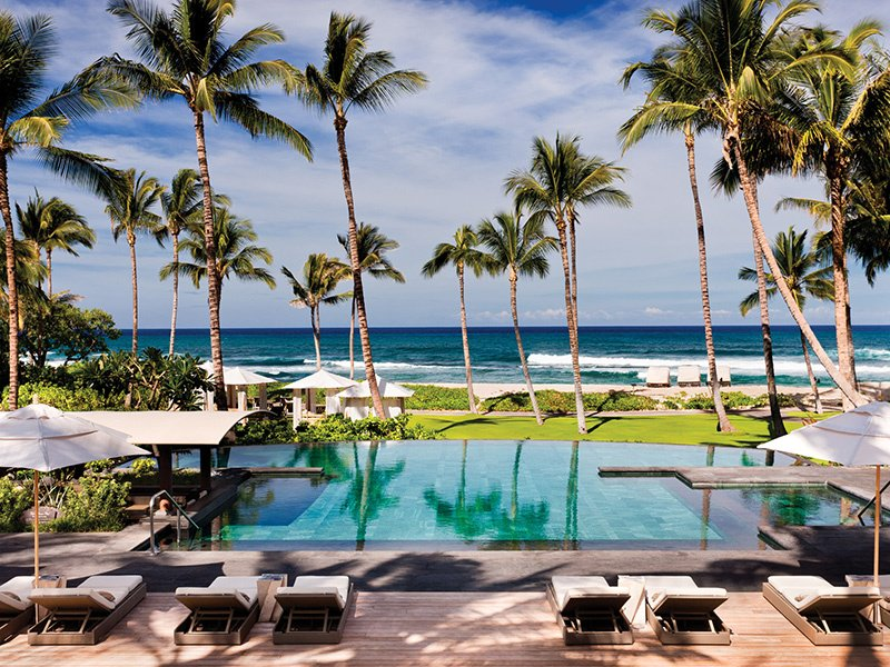 The exclusive Four Seasons Hualalai's infinity pool reflects the luxury of the entire resort, with breathtaking ocean views, island-style decor, and attentive poolside service. Photograph: Four Seasons/Don Riddle.