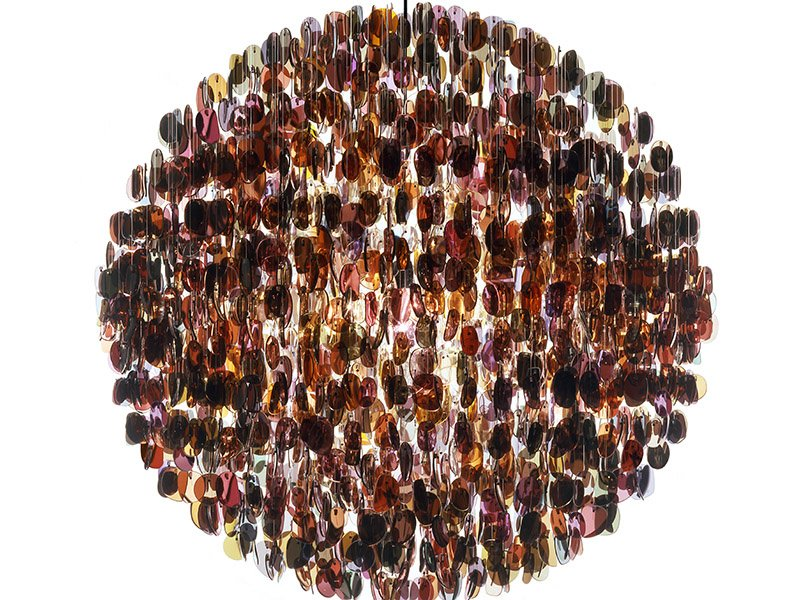 Stuart Haygarth's Optical chandelier is made from over 4,500 tinted prescriptive spectacle lenses taken from used frames. This mass of lenses resembles a disco mirror-ball, but rather than the light being reflected, it is refracted through the layers of lenses.