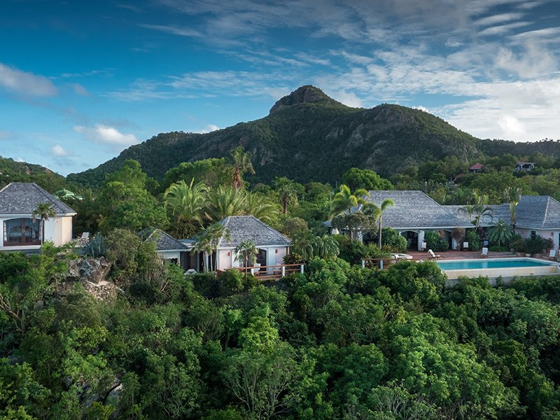 Pathways among tropical greenery surround Villa RKK, while its infinity pool overlooks the ocean.