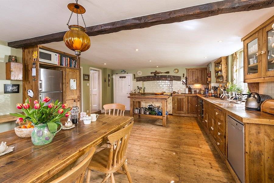 The kitchen at The Laines is at once spacious and cozy, with hardwood floors, exposed beams, wood countertops, and and a full complement of top-of-the-line appliances, including an Aga stove.