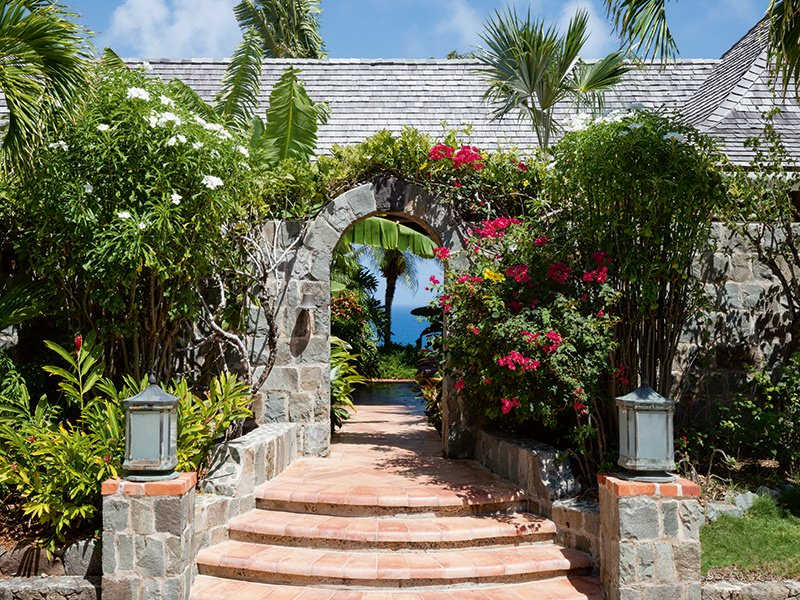 Entry to the villa is through this majestic stone archway, bordered by lush foliage and flowers.