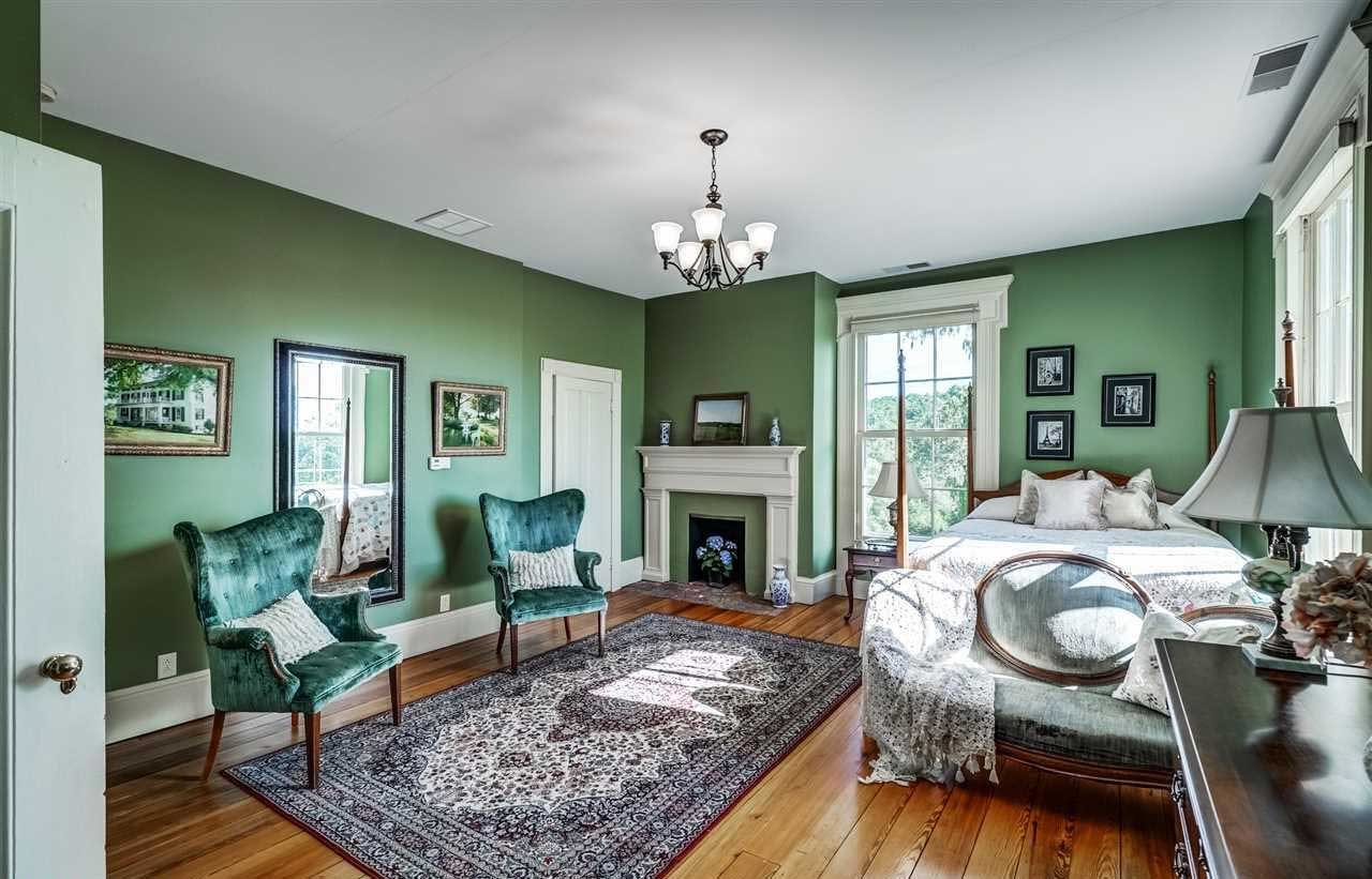 Guildford Farm Estate's master bedroom, adorned with pastel green walls and emerald-toned accents, mirrors the calming nature of its grounds, which can be viewed from the floor-to-ceiling sash window.