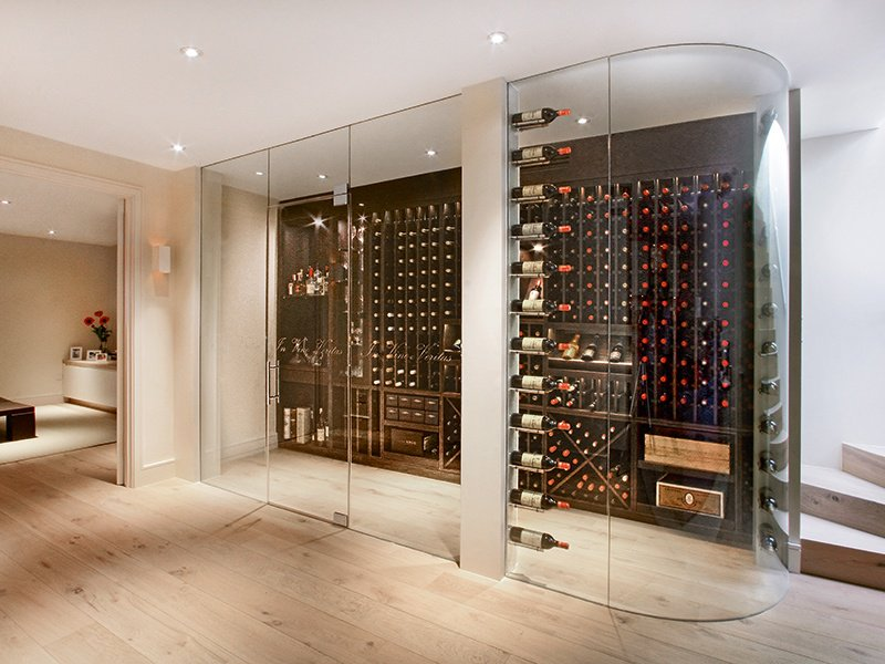 The walk-in, frameless, made-to-order wine pods by Cellar Maison are climate controlled, and can be created with curved or square glass.