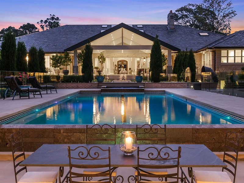 This spectacular two-story French provincial-style mansion on one of Sydney's most exclusive acreages is a paean to outdoor entertaining. The expansive interiors open out onto terraces and verandahs set up to welcome garden-party guests. Beyond this, a pool and spa sit alongside swathes of lawn, a garden gazebo, and a firepit.