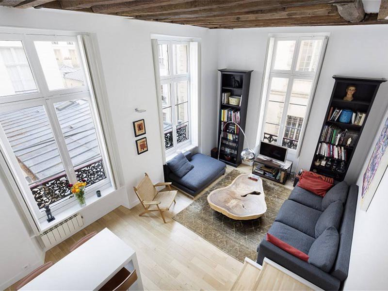 A superb triplex apartment, this three-bedroom apartment benefits from high ceilings and a prime location in Paris's historic Marais neighborhood.