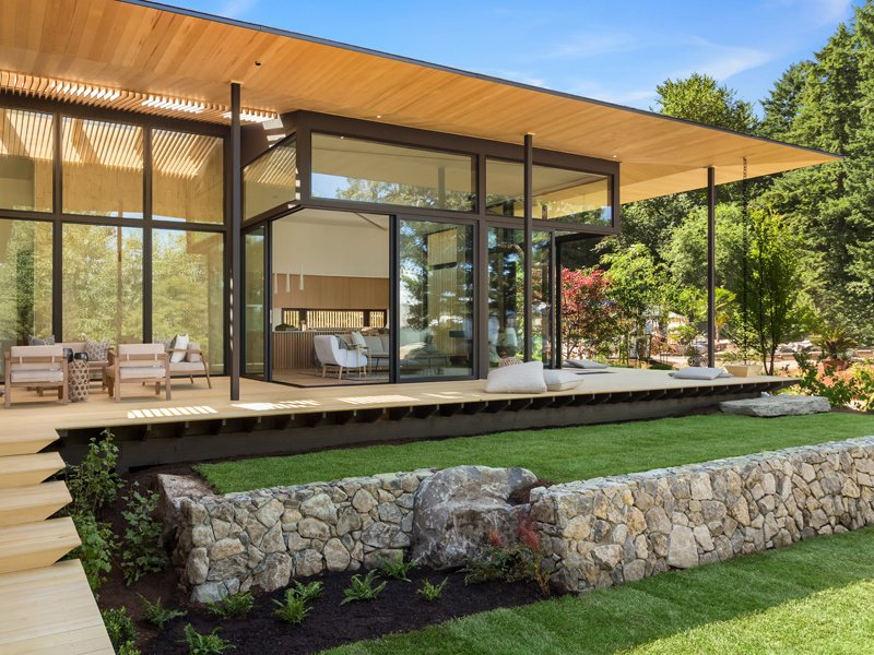 Sliding doors give direct access to the garden from every room on the ground floor, while high-performance floor-to-ceiling glass lets light in and offers year-round climate control.