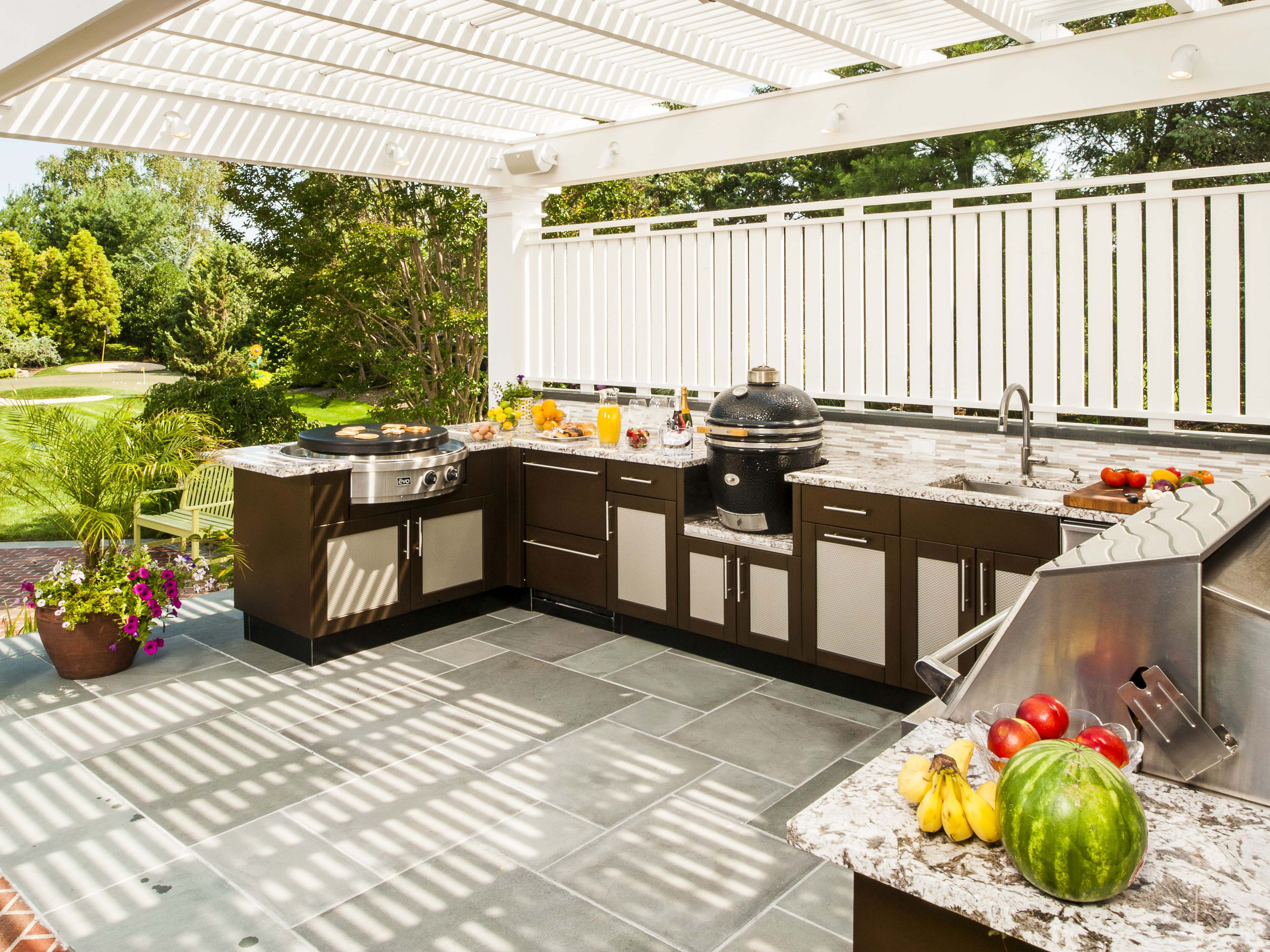 The interiors flow seamlessly into the outdoor area with this sunny creation by Brown Jordan Outdoor Kitchens in Long Island, New York.