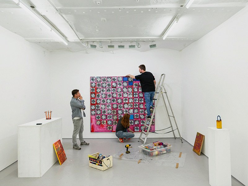 Kim Savage, director of London's FOLD gallery, looks on as contemporary artist Dominic Beattie checks his ink-and-spray-paint work Cross and Crown. Photograph and banner image: Chris Terry.