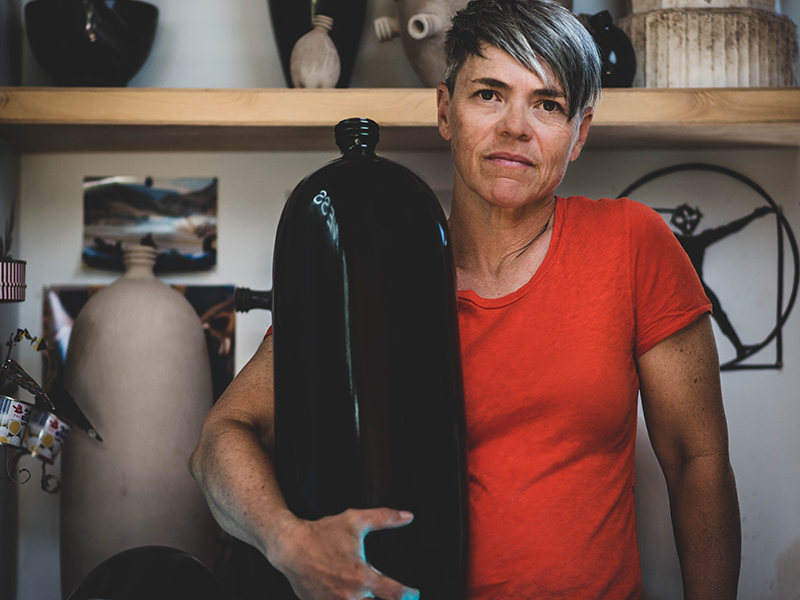Woman holding large black ceramic bottle