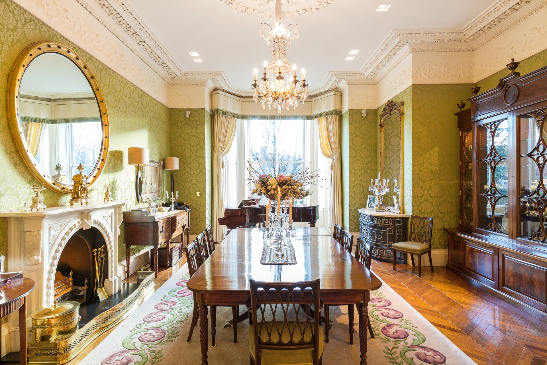 Lavish green dining room with beautiful crown molding. Filled with lots of natural light and high end furnishings.