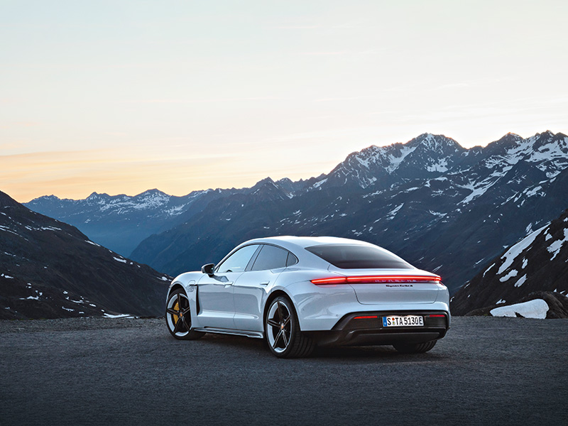 Sports car overlooking snowy mountains