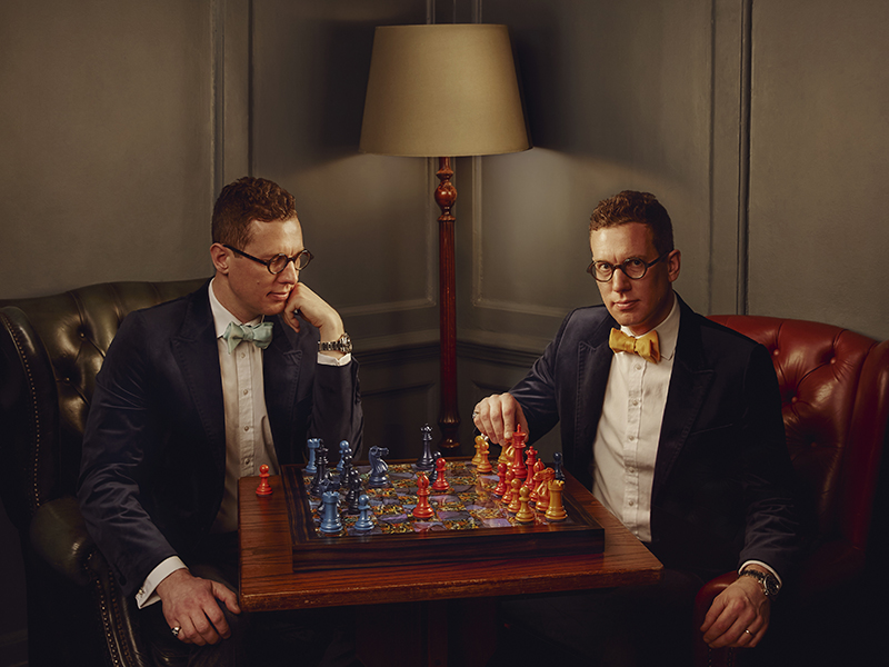 Man facing mirror image of himself, playing luxury chess sets