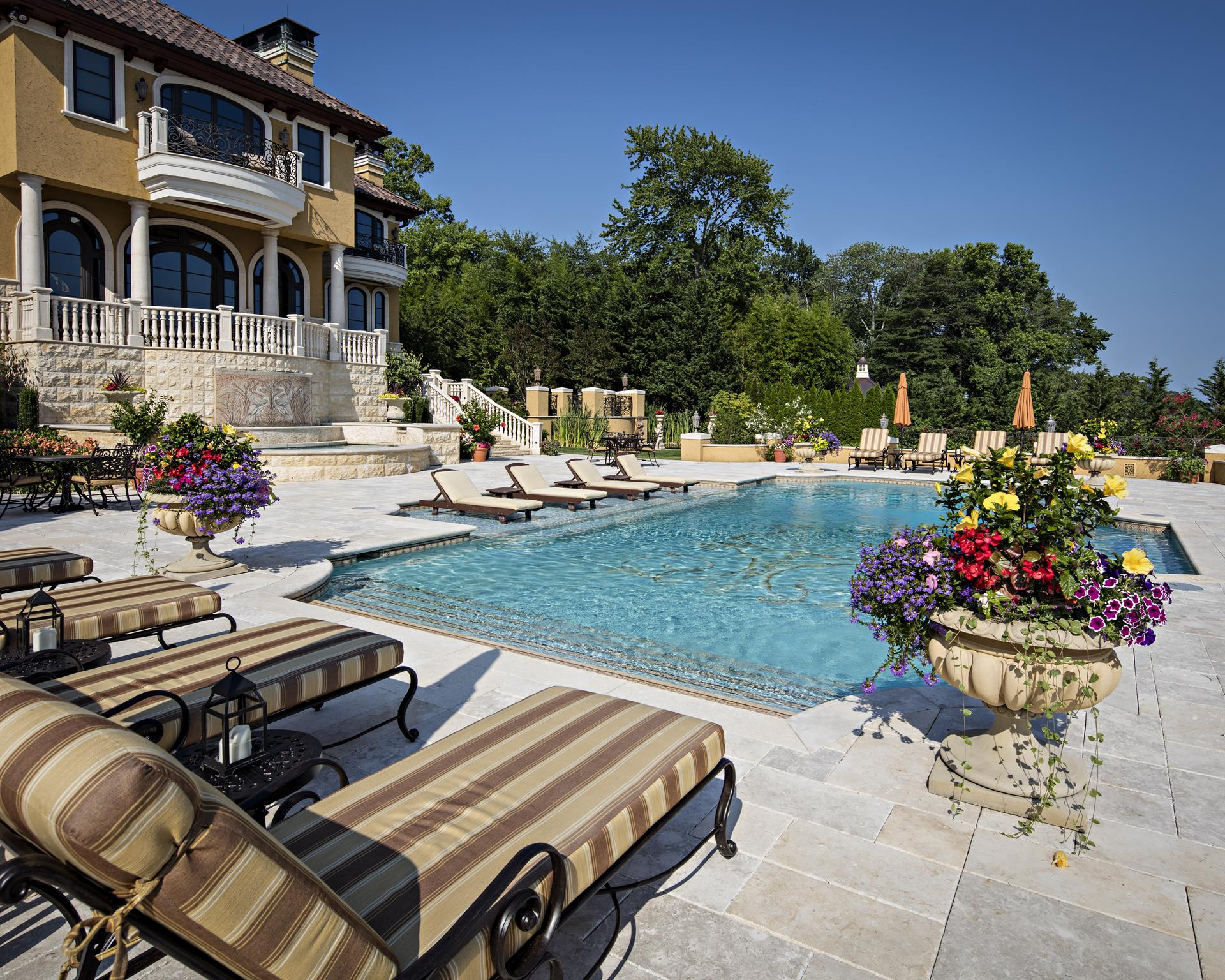 A beautiful gunite pool with a mosaic floor and lapis lazuli border is the centerpiece of this Mediterranean-style riverfront estate in Middletown, New Jersey.