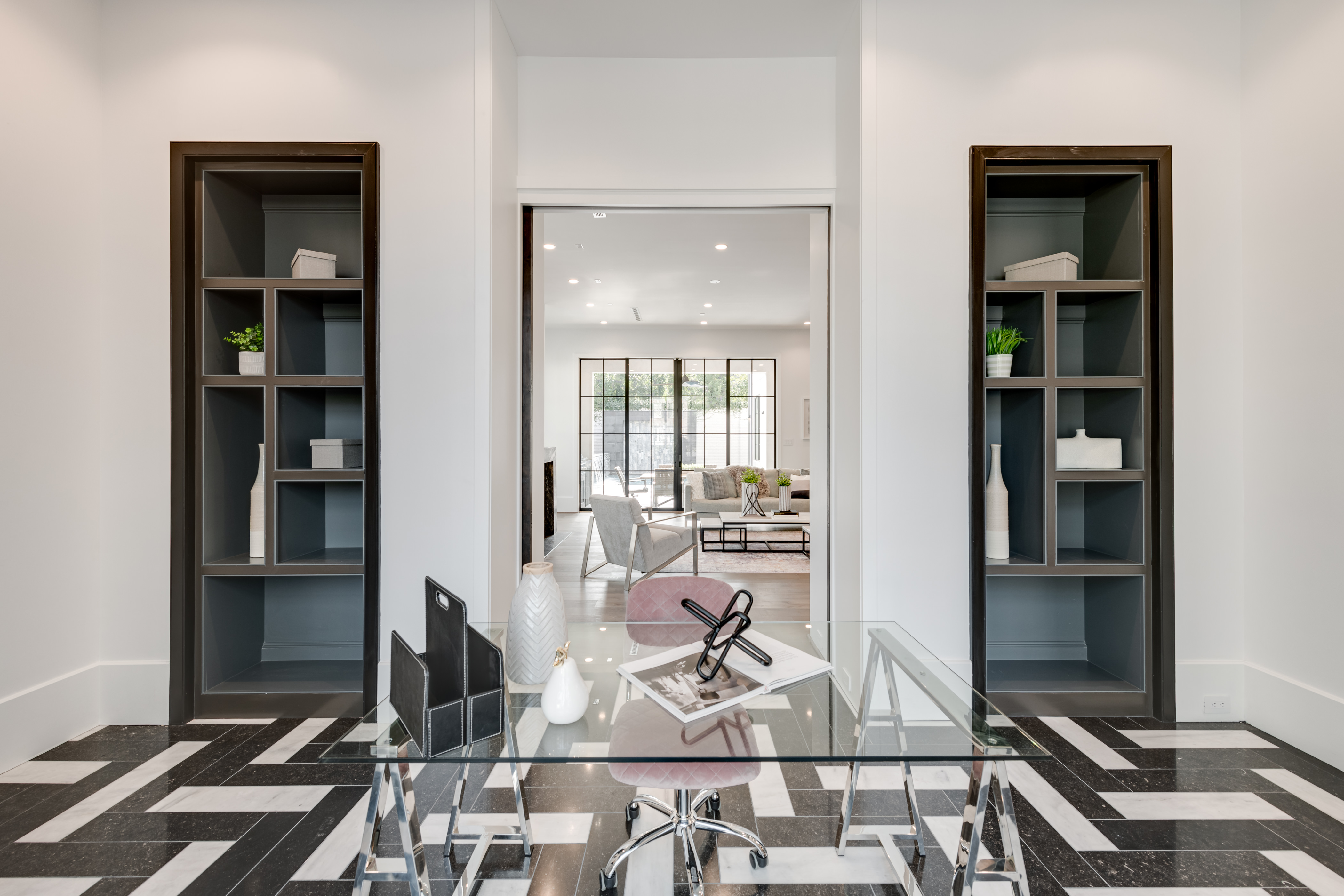 Meticulous attention to detail is evident throughout this impeccable residence in Houston's River Oaks. The light-filled living spaces include an office with a wall of windows and striking black-and-white marble floors.