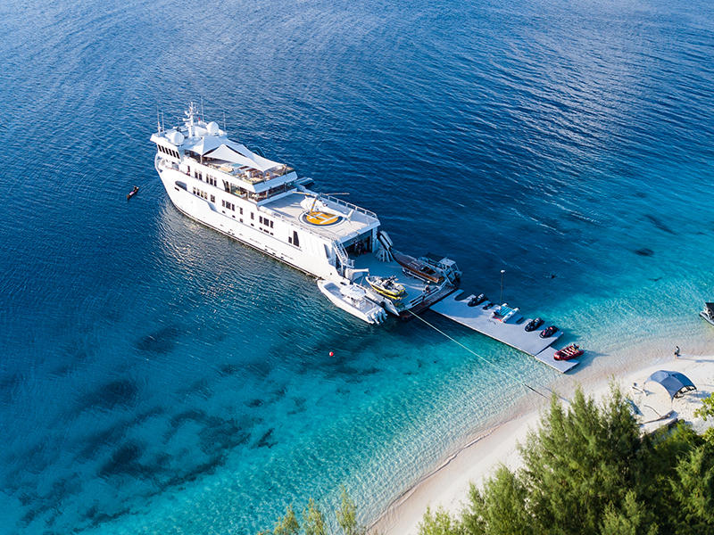 An aerial view of the SuRi superyacht moored at a white beach
