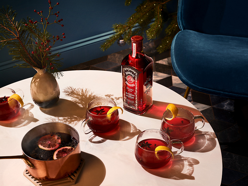 A bottle of Bombay Bramble gin surrounded by glasses of mulled punch