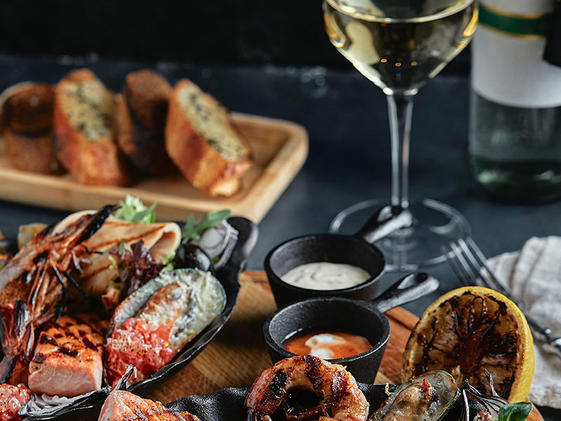 Fresh seafood and white wine on a stone table. Oysters, prawns and scallops, squids, served by the chef, beautifully laid out on plates, dark concrete