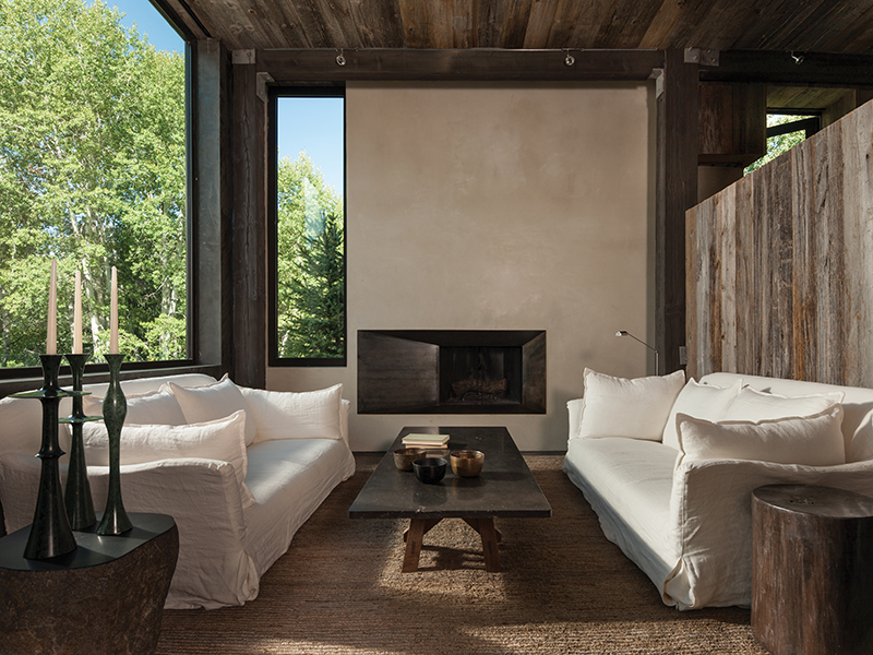 A living room with white sofas, large garden-facing windows, and reclaimed wood walls