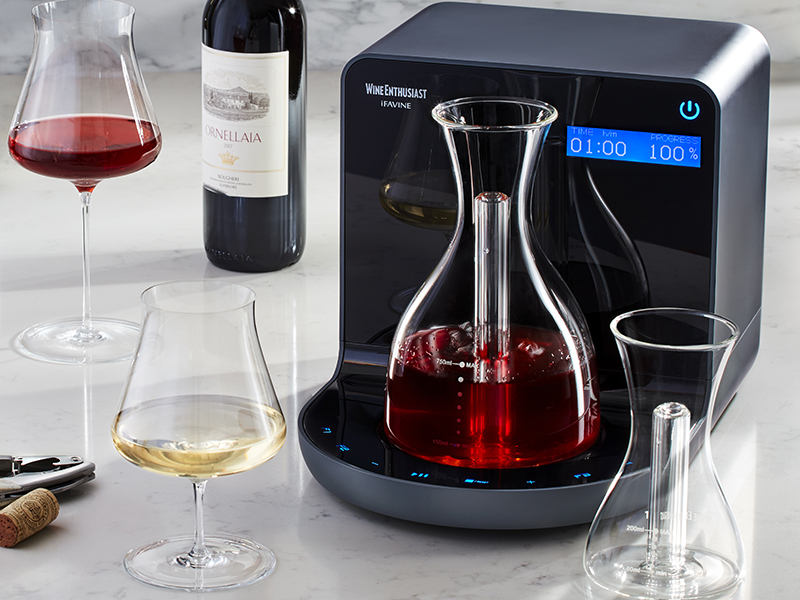 A decanter sitting upon the black iSommelier gadget