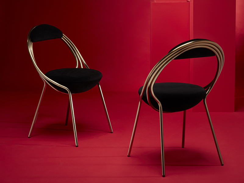 Statement pieces of black and gold chairs on red background
