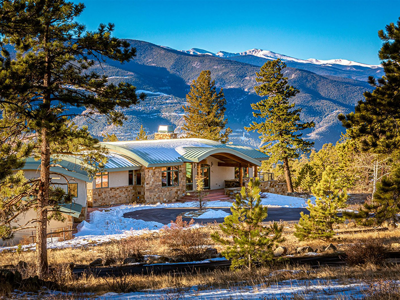 A view of a home surrounded by snowy mountains in Denver