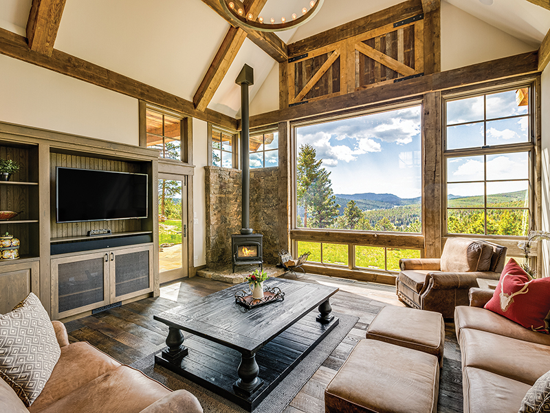 View from a rustic -lodge style living room onto mountains and fir trees
