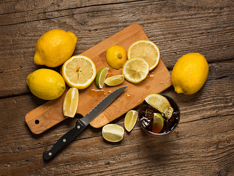 Lemons, knife and lemon slices on chopping board, with cocacola glass on wooden table.