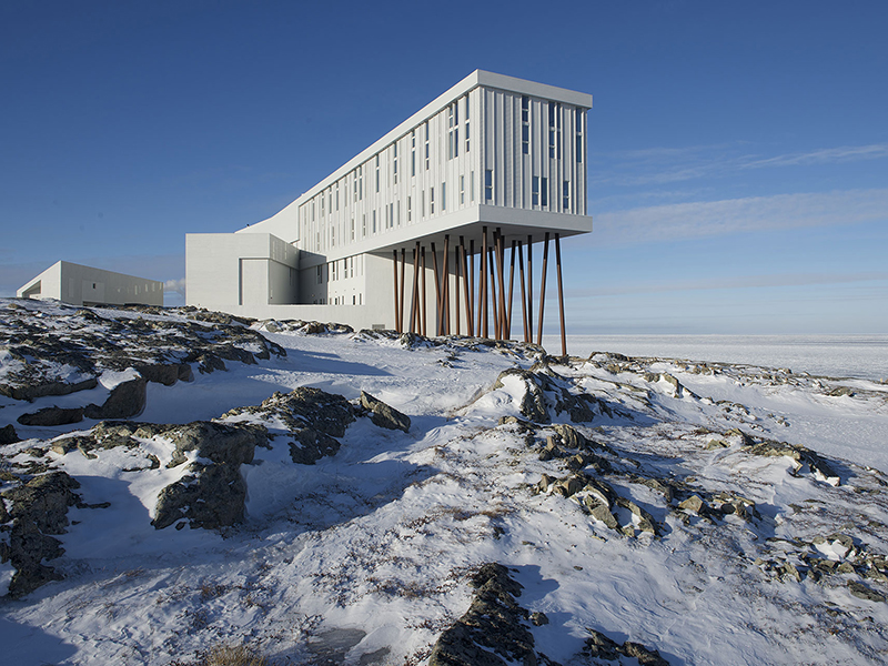 Fogo Island Inn, a dramatic cantilevered structure in the snow, is a fantastic example of green travel practices