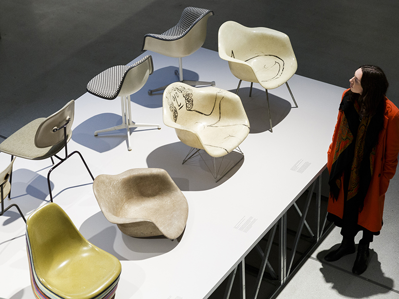 A woman views examples of Eames chairs at The World of Charles and Ray Eames exhibition at the Barbican Art Gallery at Barbican Centre on October 20, 2015 in London, England.