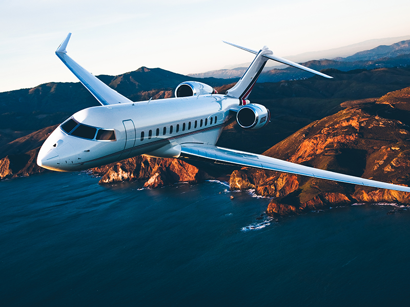 A NetJets plane flies overthe sea with mountains in the background