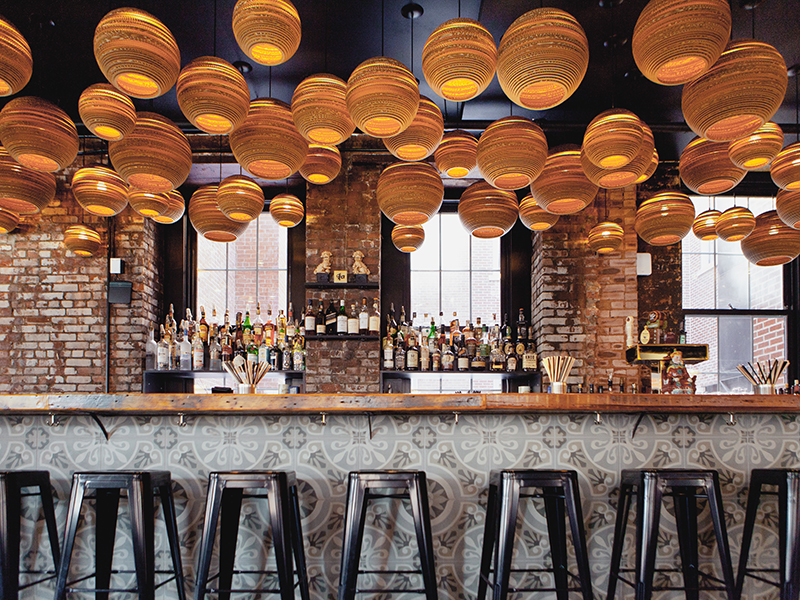 A large number of spherical Scraplights hang over a bar