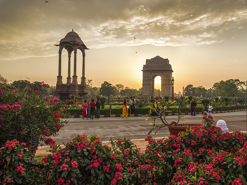 The India Gate at sunset with flowers in the foreground