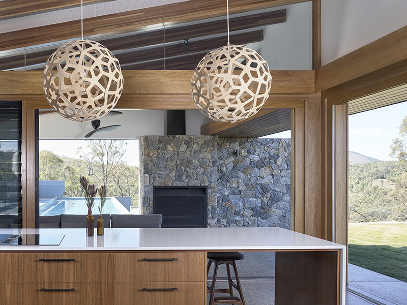 Two coral lightshades hang over a kitchen counter in a modern home