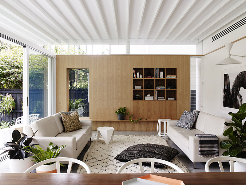 A living room with plants, white sofas and large open windows
