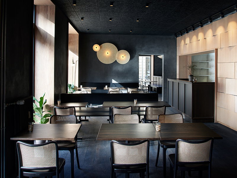 A restaurant with dark walls and natural wood throughout