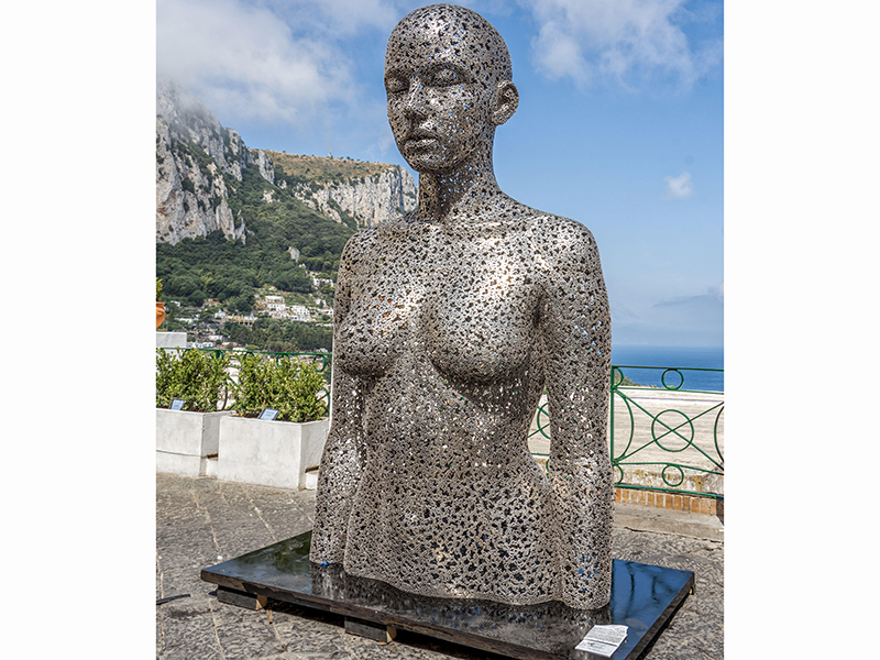 A large sculpture of the female form with the sea and ocean in the background