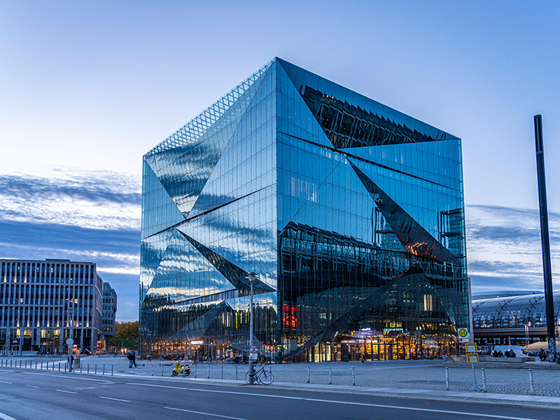 The reflective faceted glass exterior of Cube Berlin at sunset
