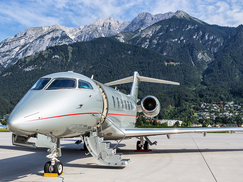 A private jet on a runway with mountains in the background