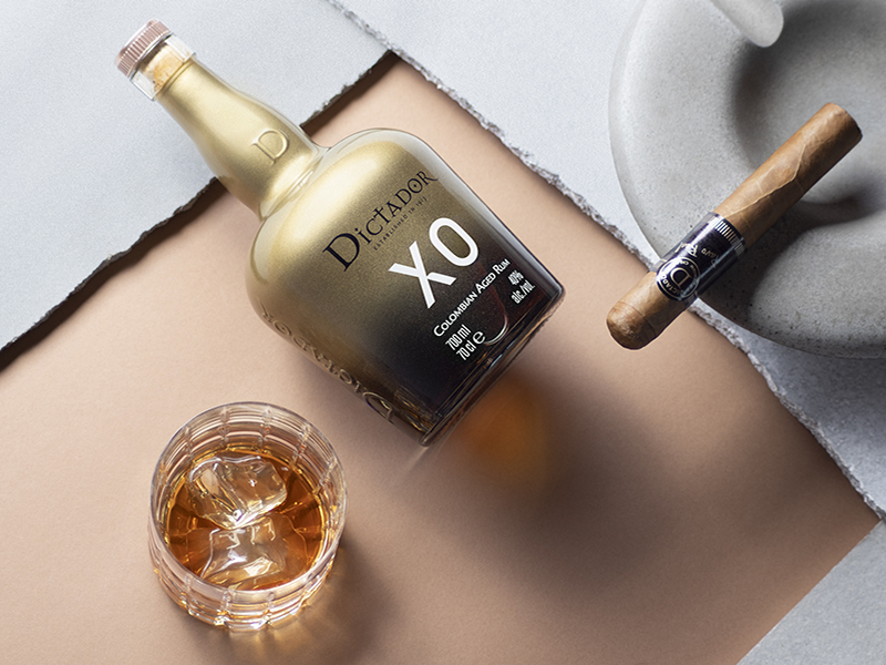 Glass and bottle of Dictador rum, served with a cigar