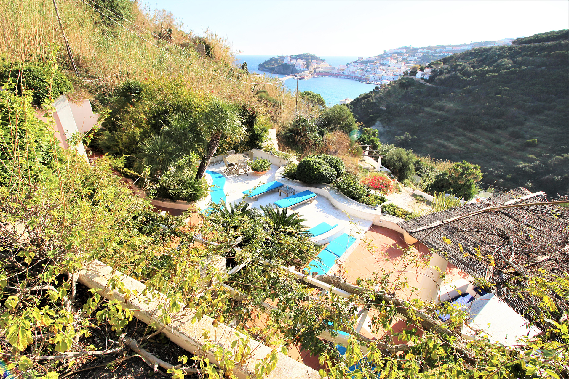 A view onto a porch with swimming pool and the bay and harbor below