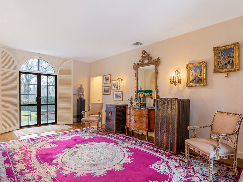 A foyer with elegant red Persian carpet and two large Louis Vuitton trunks