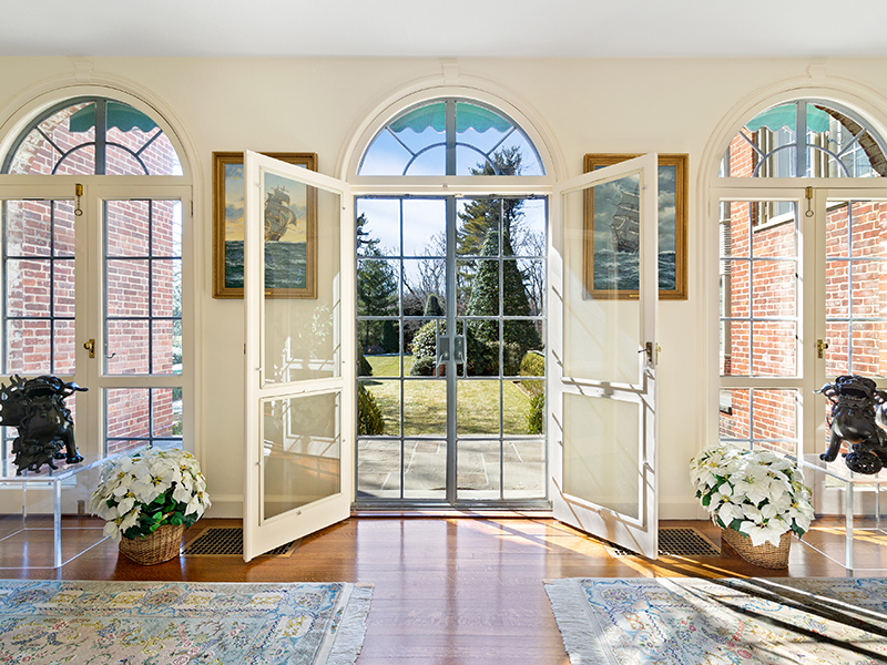 Large french doors opening onto green lawn