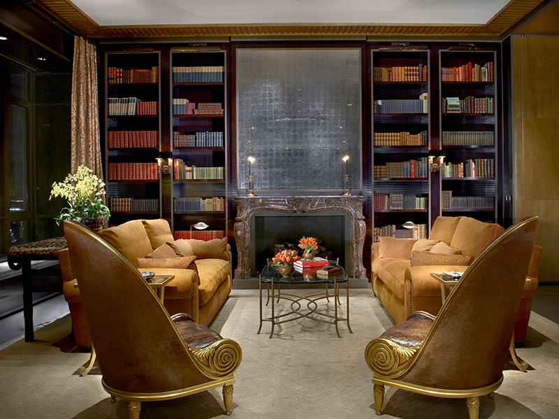 A grand library room in tones of gold and dark wood