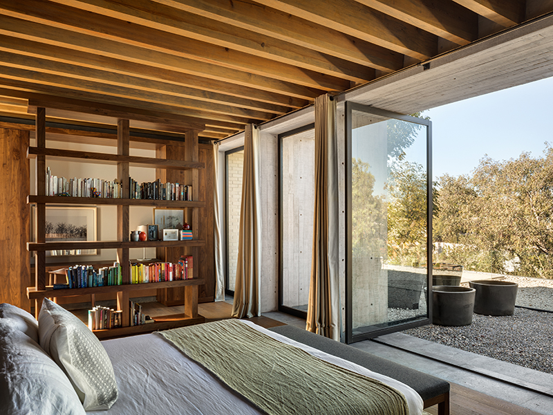 A bedroom with a large glass wall opening onto a patio