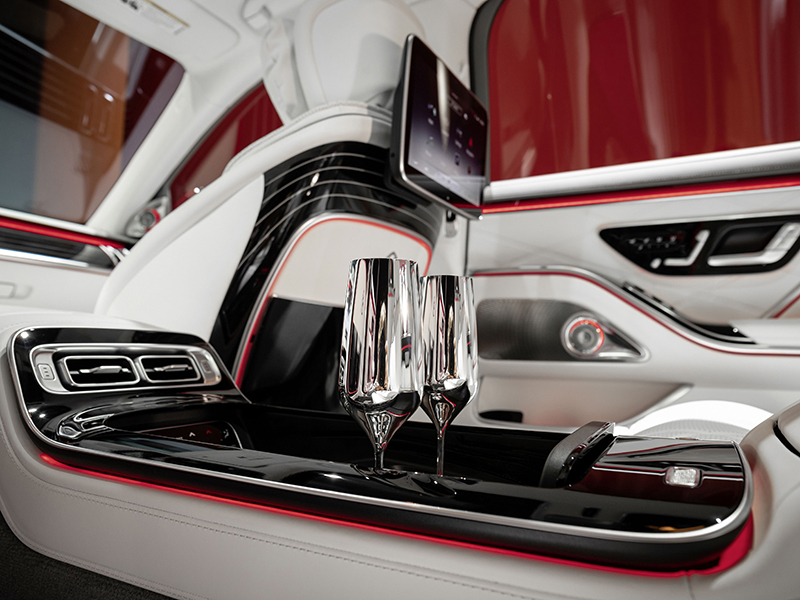 The center console of a Maybach with two silver champagne flutes