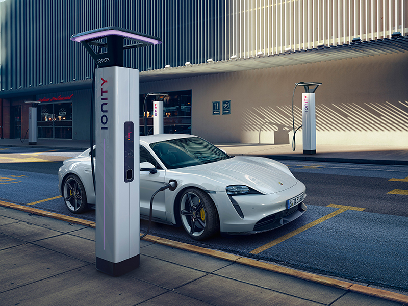 A white electric Porsche Taycan charging on a city street