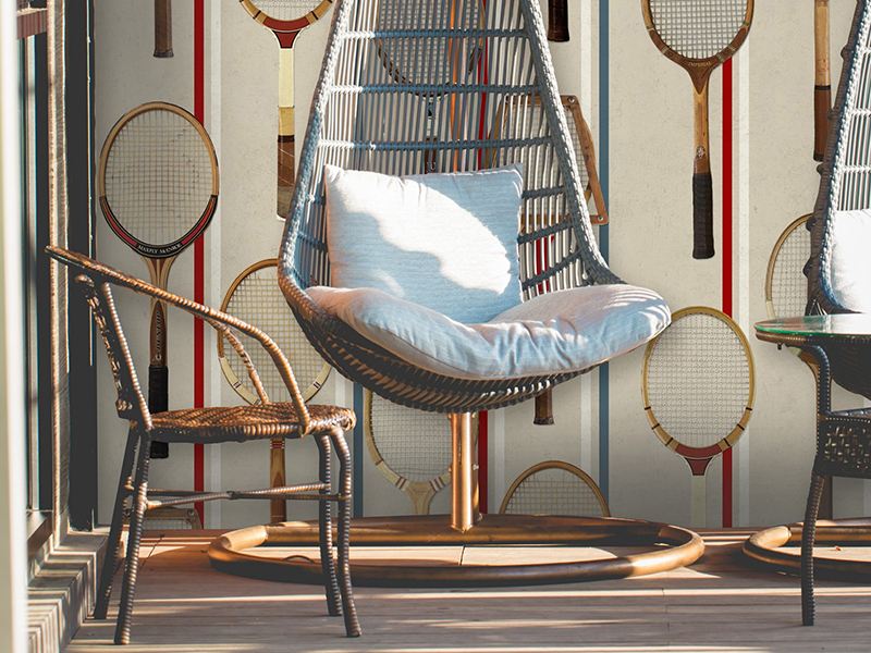 A wicker chair in front of tennis-themes wallpaper